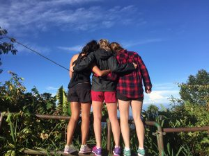 Photo taken from behind of Three girls hugging and watching nature