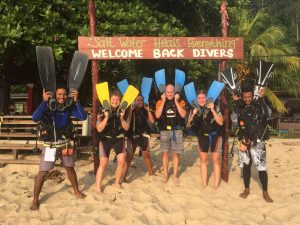"""Group of friends holding snorkeling flippers in front of a sign saying """"Salt Water Heals Everything"""" """"Welcome back divers"""""""