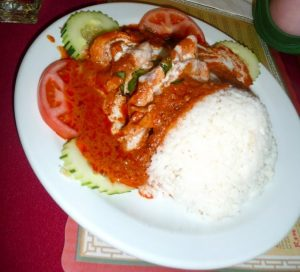 white rice topped with red sauce. cucumbers and tomatoes